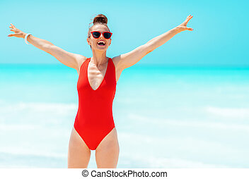 smiling modern woman in red swimsuit on seashore rejoicing
