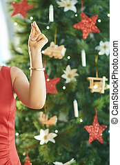 smiling modern woman with fingers snapping near Christmas tree