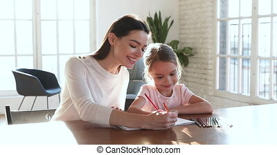 Smiling mom teaching kid girl drawing with color pencils ...