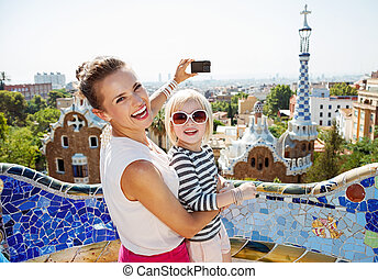 Smiling mother and baby taking photos with camera at Park Guell