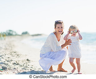 Smiling mother and baby wearing sunglasses on beach