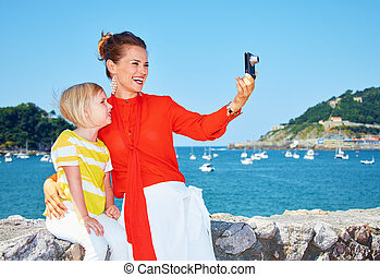 Smiling mother and child taking photo in front of lagoon