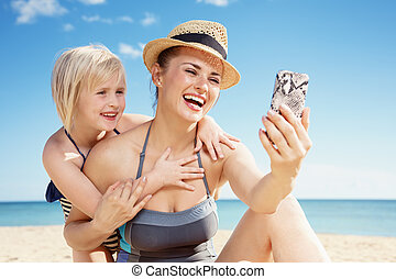 smiling mother and child taking selfie with phone on seacoast