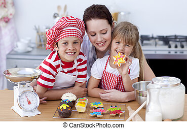 Smiling mother and children baking in the kitchen