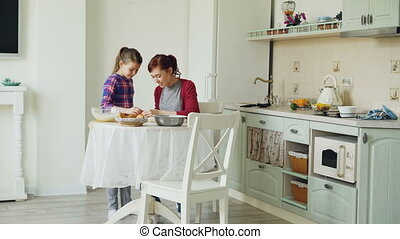 Smiling mother and cute daughter making cookies together using dough while sitting in modern kitchen at home. Family, food and people concept