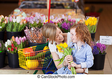 Smiling mother and daughter buying tulips