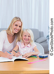 Smiling mother and daughter drawing together