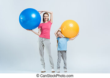 smiling mother and daughter holding fitness balls on white