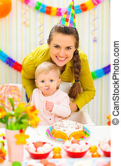 Smiling mother and eat smeared baby on birthday celebration...