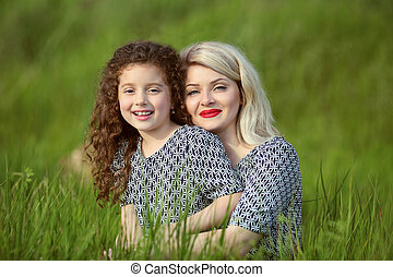 Smiling mother and funny daughter in green grass field. outdoor family portrait
