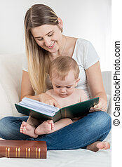 Smiling mother and her 9 months old baby boy sitting on sofa and reading big book