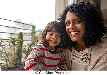 Smiling mother and her cute daughter sitting together at home