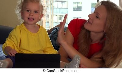 Smiling mother and her cute toddler daughter using tablet at...