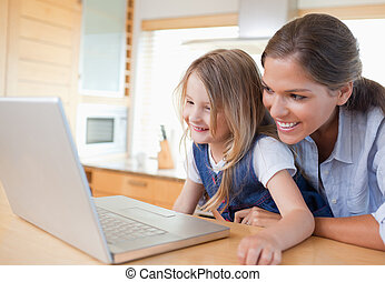 Smiling mother and her daughter using a notebook