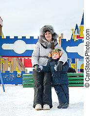 Smiling mother and son in a winter playground