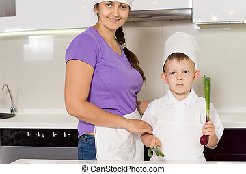 Smiling mother and son in chefs outfits