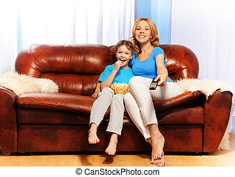 Smiling mother and son watch television at home