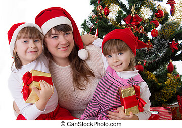 Smiling mother and two daughters under Christmas tree