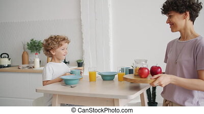 Smiling mother attractive young lady is bringing breakfast cereal and apples for happy child sitting at table at home. Lifestyle, food and people concept.