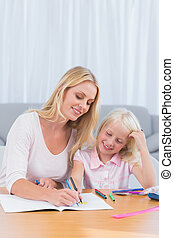 Smiling mother drawing with her daughter