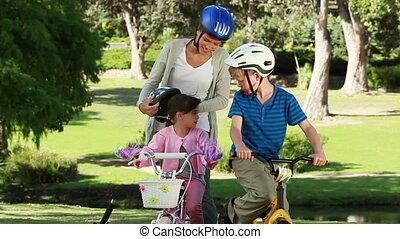 Smiling mother fastening the helmets of her children