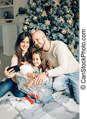 smiling mother, father and little girl making selfie with camera