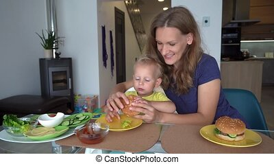 Smiling mother feeding little son with big hamburger. Gimbal motion