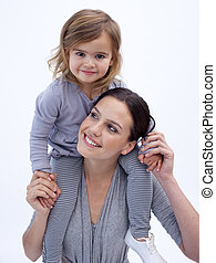 Smiling mother giving her daughter piggyback ride
