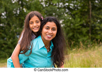 Smiling mother giving piggyback to daughter