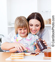 Smiling mother helping her daughter prepare the breakfast