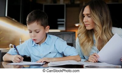 Smiling mother helping his son doing homework, dictates the text to help you write sitting at the table in the kitchen.