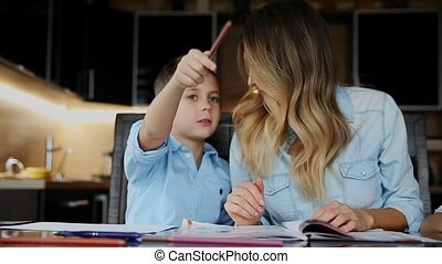 Smiling mother helping his son doing homework, dictates the...