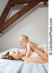 Smiling mother holding cute baby in bed