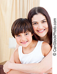 Smiling mother hugging her son