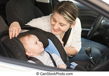 Smiling mother in car having her baby boy in safety seat