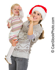 Smiling mother in Christmas hat and baby girl pointing up on copy space
