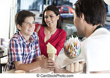 Smiling Mother Looking At Son Receiving Ice Cream From...