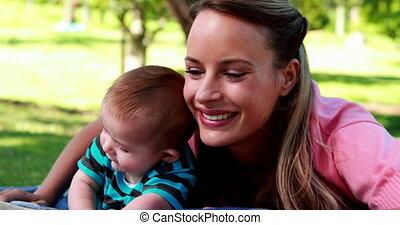 Smiling mother lying on picnic blan