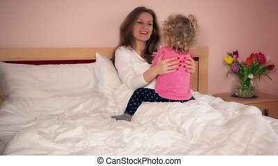 Smiling mother mom and her cute daughter girl have fun in bed