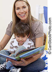 Smiling mother reading a book with her son