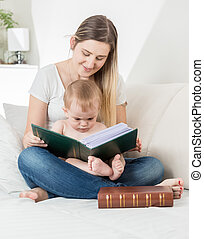 Smiling mother reading story to her 9 months old baby boy