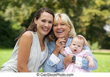 Smiling mother sitting with grandmother and child