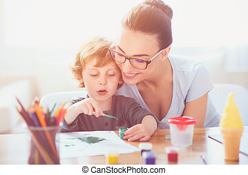 Smiling mother teaching her son to draw