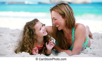 Smiling mother tickling her daughter