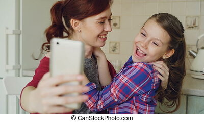 Smiling mother together with funny playful cute daughter...