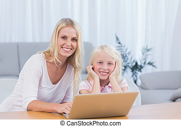 Smiling mother using laptop with her daughter