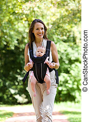 Smiling mother walking outdoors with baby in sling