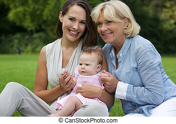 Smiling mother with child and grandmother outdoors