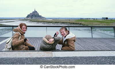 smiling mother with daughters and view of Mont Saint Michel