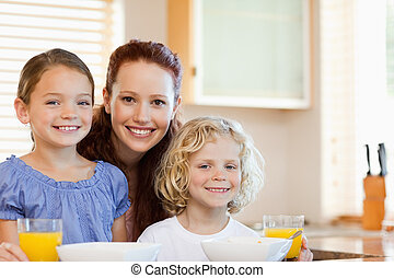 Smiling mother with her children in the kitchen